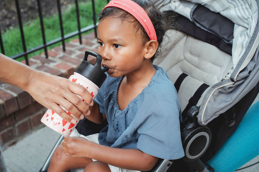 child drinking from a water bottle